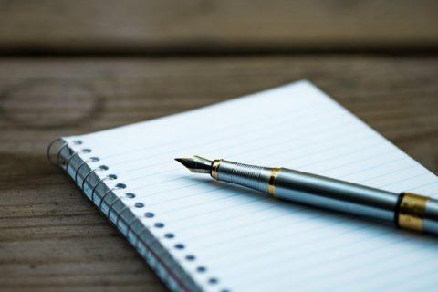 Bloc notes posé sur une table avec un stylo