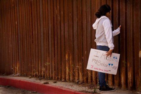 Jeune fille devant le mur de séparation Etats-Unis / Mexique