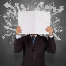 Homme tenant un livre blanc ouvert devant son visage