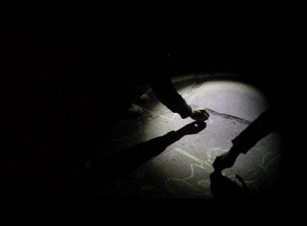 Eclairés seulement d'un rond de lumière, des mains dessinent à la craie sur les trottoirs.