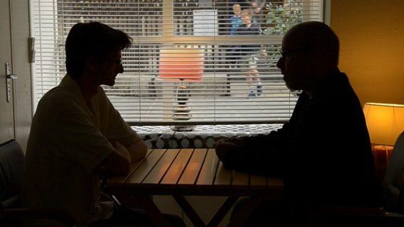 deux personnes dans l'obscurité assises à une table et en train de se parler