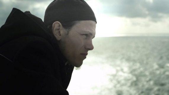 Portrait d'un jeune homme de profil regardant la mer
