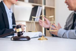 deux personnes en train de discuter autour d'une table avec une balance et un marteau (symbole de la justice)