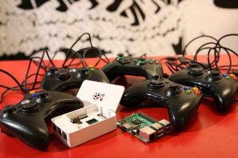Une Recalbox et des manettes de console sur une table, devant une fresque en noir et blanc