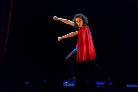 Photo de Laureline Kuntz sur scène avec une cape rouge