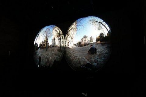 Vues binoculaires issues d'une caméra 360 d'une rue avec un jeune homme assis