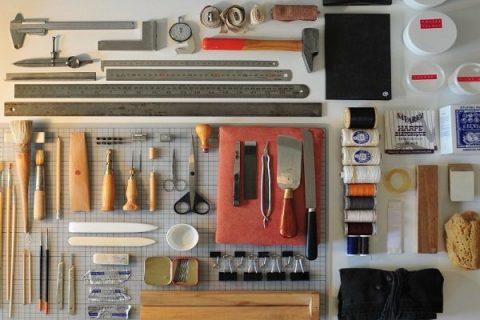 Photographie de matériel de reliures (nombreux outils, fils, colles...)