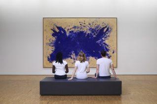 Trois personnes sur un banc assises devant une oeuvre du Centre Pompidou