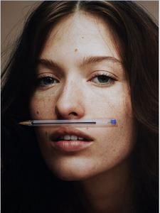 jeune femme avec un stylo en guise de moustache