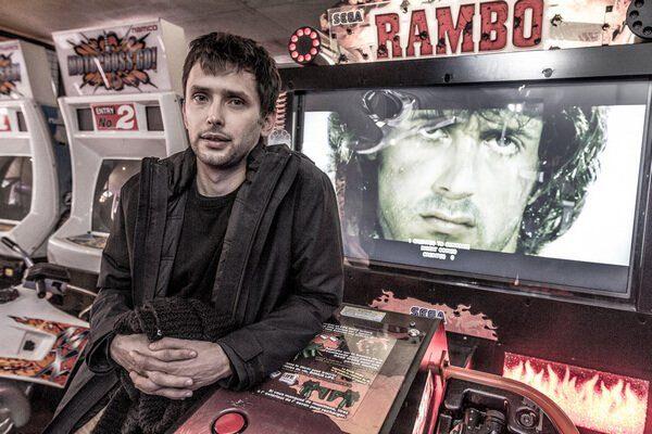Portrait de Benjamin Nuel accoudé sur une borne d'arcade du jeux Rambo