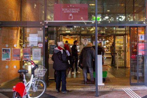 Photo de l'entrée d'une bibliothèque avec des usagers entrant et sortant.
