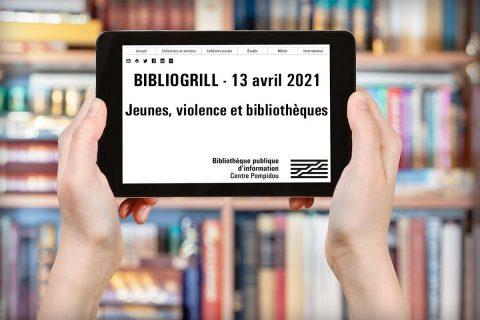 Deux mains tiennent une tablette devant une bibliothèque de livres