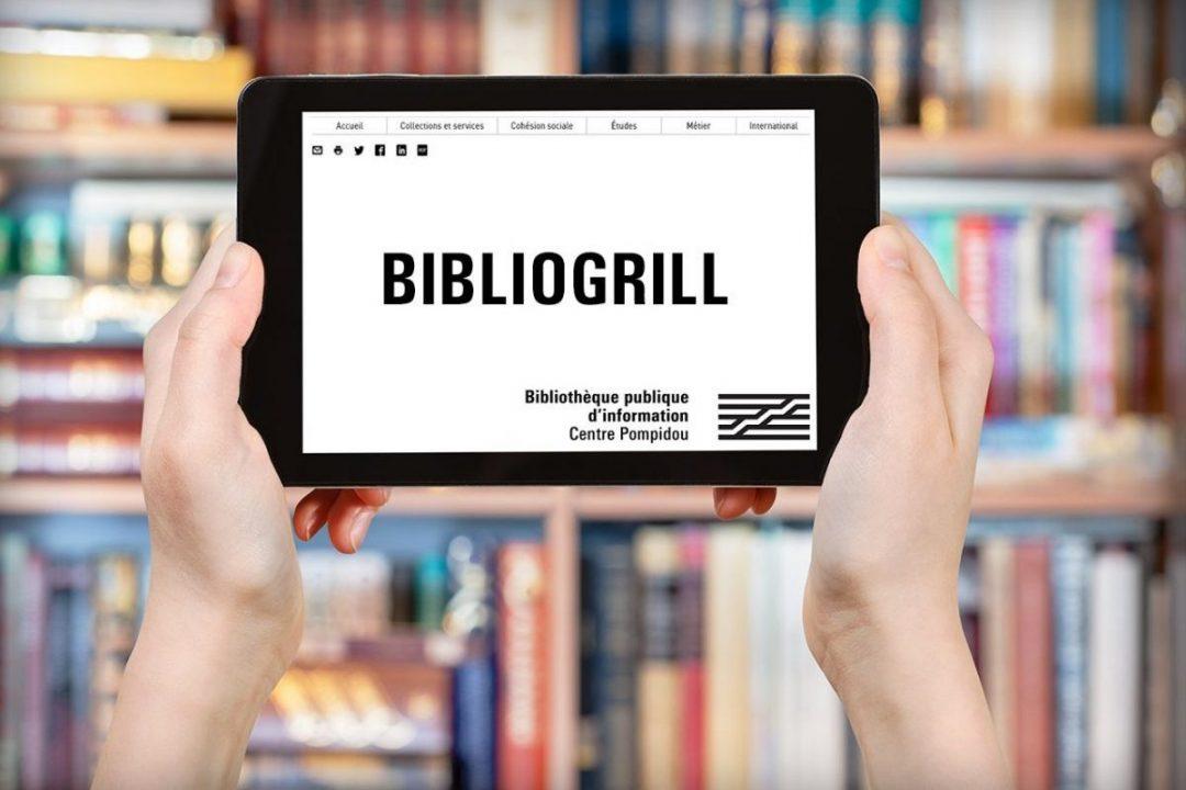 Deux mains portent une tablette devant une bibliothèque de livres sur laquelle est inscrit le nom Bibliogrill