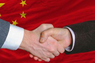 photo d'une poignée de main devant le drapeau chinois