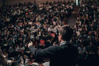 Un homme de dos, le micro à la main, s'adresse à des étudiants rassemblés dans une salle comble.