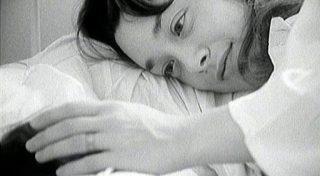 Une femme allongée caresse la tête d'un nouveau-né